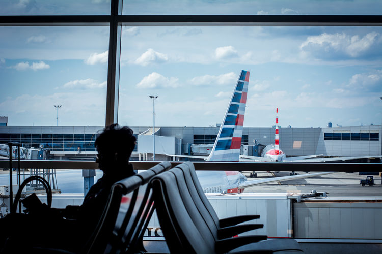 Rear view of woman sitting at airport against sky in city