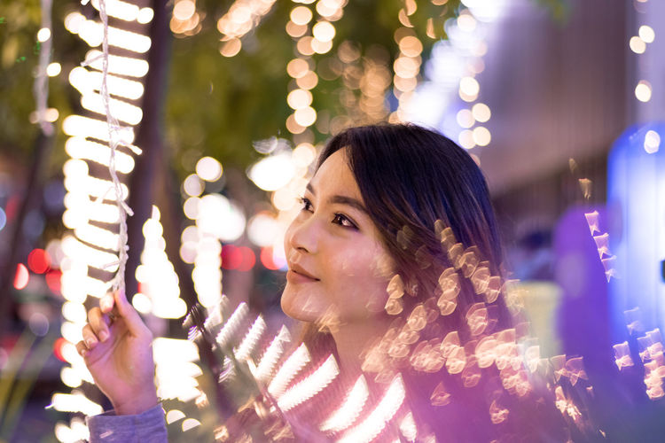 Close-up of young woman amidst illuminated lights