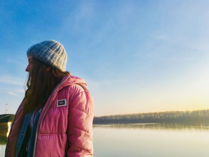 Water Sky One Person Lake Real People Hat Clothing Standing Beauty In Nature Nature Knit Hat Leisure Activity Casual Clothing Lifestyles Women Warm Clothing Rear View Looking At View Adult Outdoors