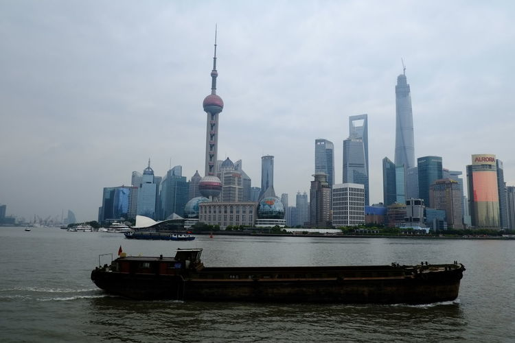Boat Sailing On River Against Shanghai World Financial Center In City