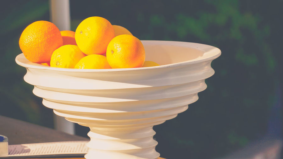 Close-up of oranges in fruit bowl on sunny day