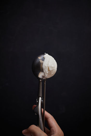 Cropped hand holding ice cream against black background