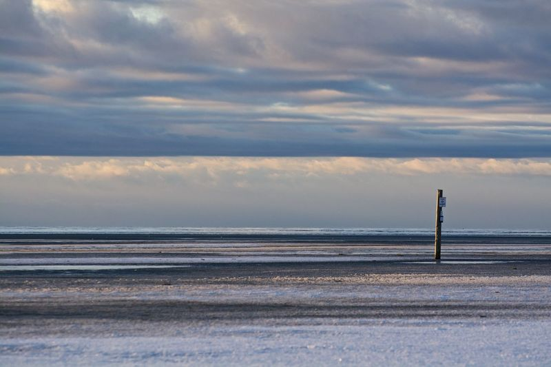 Wooden post on snow covered field against cloudy sky
