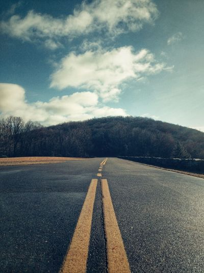 Surface level of empty road against cloudy sky