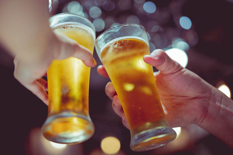 Cropped Hands Of People Toasting Beer Glasses In Bar