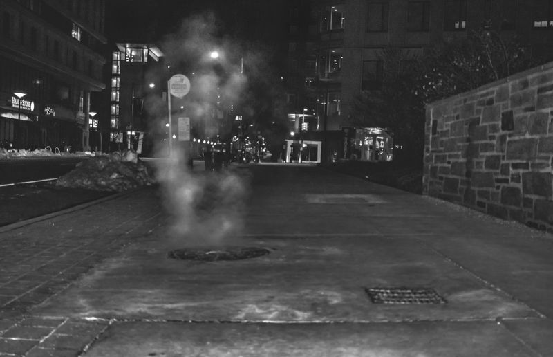 Exhaust and steam escaping at night through steam pipes and man hole covers and smoke stacks in Philadelphia, Pennsylvania City Life City Lights At Night City Lights By Night Cityscape EyeEm Best Shots Manhole Cover Pennsylvania Philadelphia Sidewalk Smoke Steam Architecture Bnw Bnw_collection Building Exterior Built Structure City Dodge And Burn Howard Roberts Illuminated Night Outdoors Real People Smoke - Physical Structure Steam