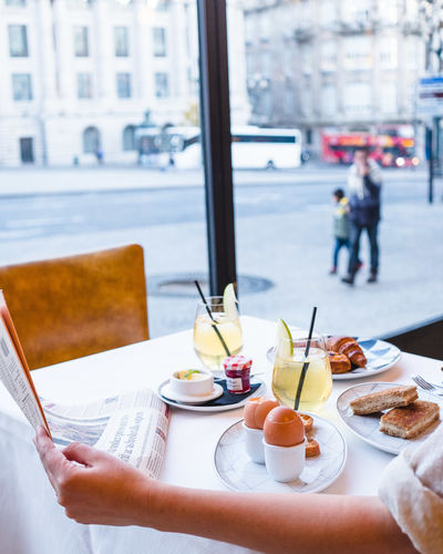 Table Food And Drink Real People Human Hand Food Business Indoors  One Person Focus On Foreground Lifestyles Incidental People Architecture Window City Freshness Day Hand Drink Holding Glass Breakfast Window View Hotel