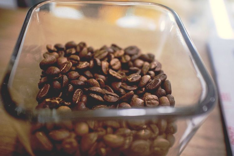 Coffee beans in bowl on table