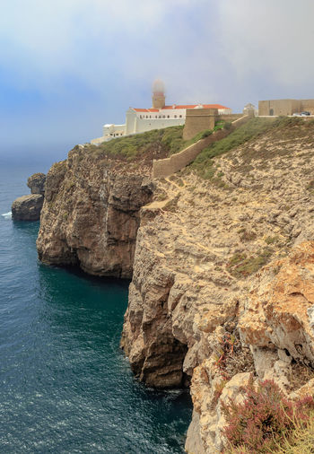 The coast at the lighthouse of Cabo sao Vicente Algarve Lighthouse Portugal Algarve, Portugal Built Structure Cabo São Vicente Cloud - Sky Fog Foggy Nature Outdoors Rock Rock - Object Rock Formation Scenics - Nature Sea Sky Summer Travel Water Waterfront