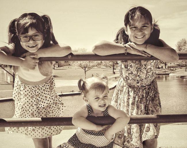 Siblings leaning on railing against sky