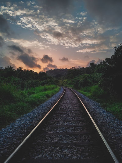 Surface level of railroad track against sky during sunset