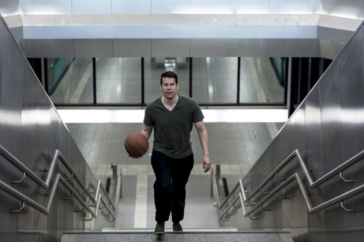 Handsome adult holding a basketball walking up the stairs. Adult Athletic Basketball Long Shot Man Public Transportation Sportsman Stairs Steps Underground Ball Casual Clothing Caucasian Ethnicity High Angle Interior Design Model Posing For The Camera Sports Sporty Stairwell Sweatpants T-shirt Urban Walking Walking Up