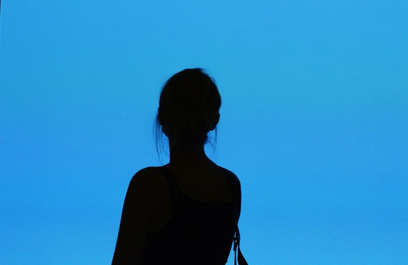 Rear view of silhouette woman standing against blue background