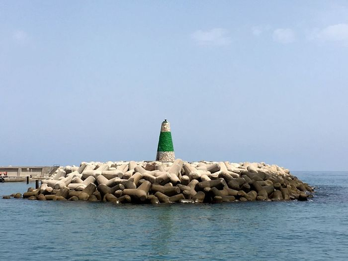 Lighthouse on tetrapods against sky