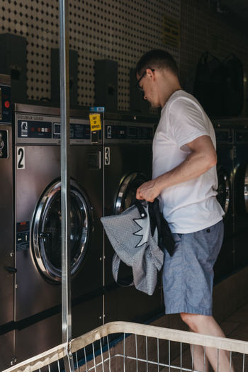 Man loading clothes in a washing machine at Laundromat, New York, USA. New York New York City USA United States Travel Tourism Laundry Laundromat Laundry Day Man Manhattan One Person Lifestyles Real People Casual Clothing Washing Machine Side View Appliance Indoors  Young Men Three Quarter Length Leisure Activity Chores Real Life People Watching