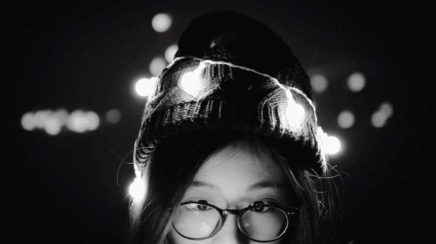 Close-up portrait of girl wearing eyeglasses with illuminated string lights
