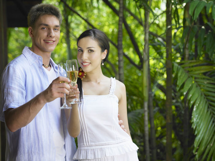 Portrait of smiling young couple with drink standing against plants