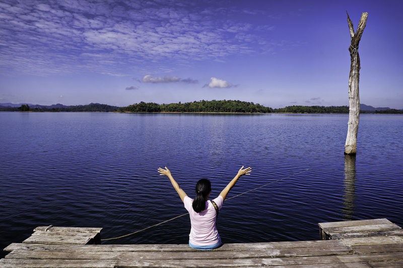 Rear view of woman with arms raised sitting on pier over lake against sky