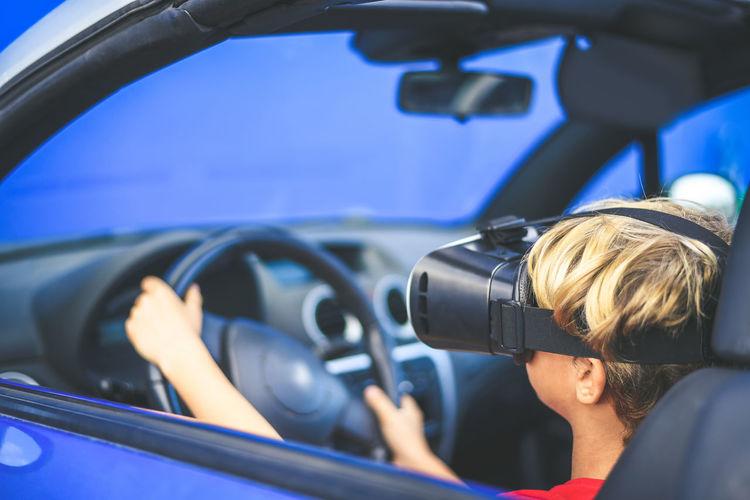 Boy wearing virtual reality simulator sitting in car