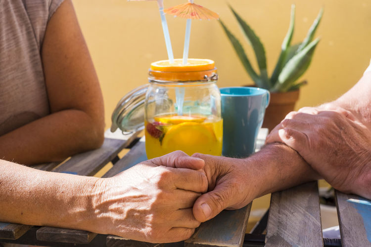 Close-Up Of Couple Holding Hands On Table At Sidewalk Cafe