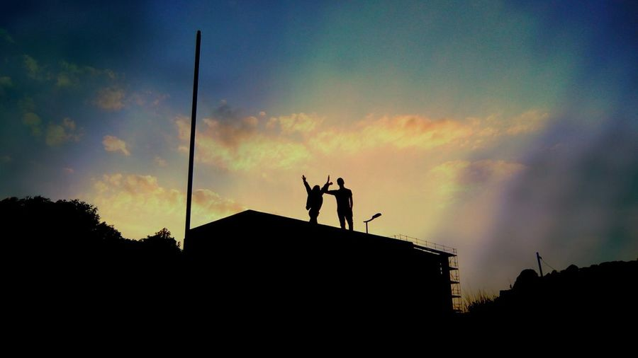 Low angle view of silhouette men against sky during sunset