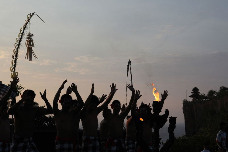 Tribal Performing Traditional Dance Against Sky During Sunset
