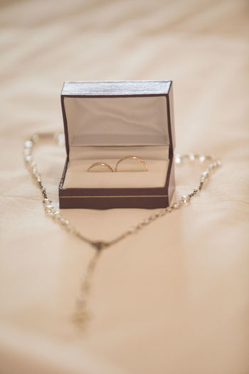 Close-up of wedding rings and necklace