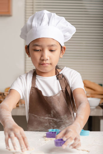 Close-up of girl preparing food at kitchen