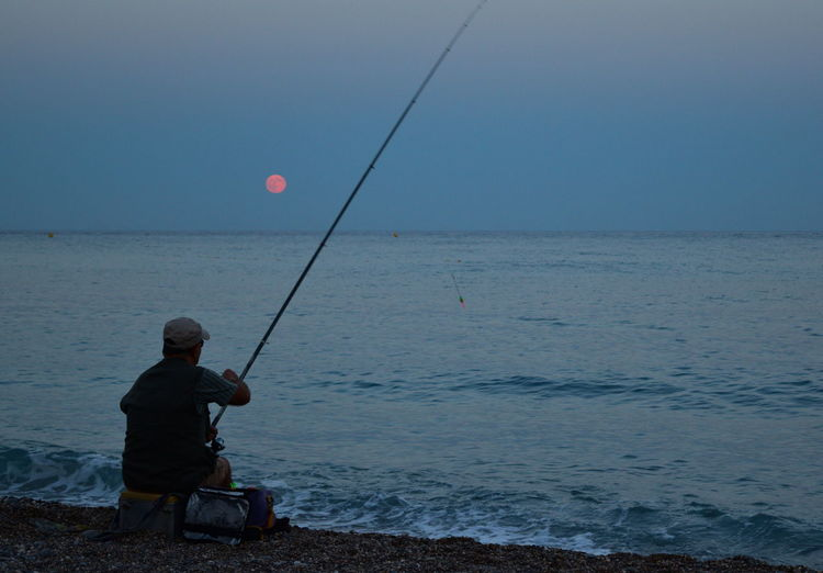 Rear view of man fishing while sitting at beach against clear sky during sunset