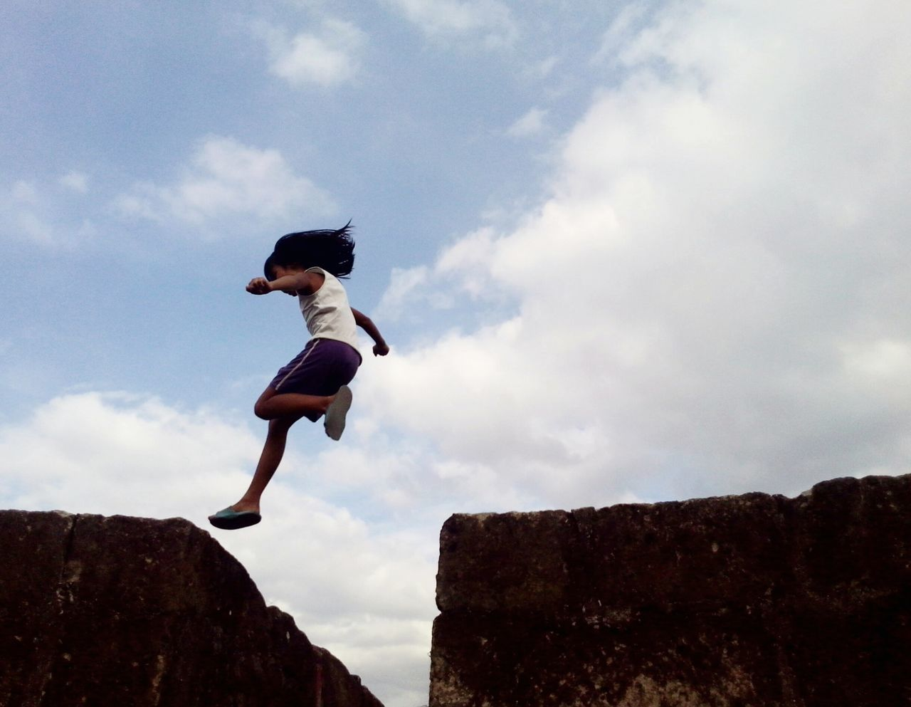LOW ANGLE VIEW OF YOUNG MAN JUMPING AGAINST CLOUDY SKY