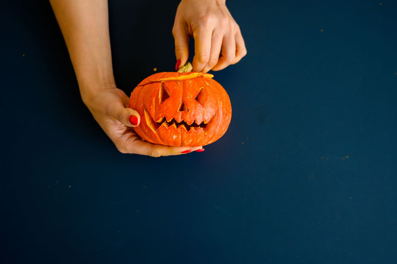 Midsection of person holding pumpkin against black background