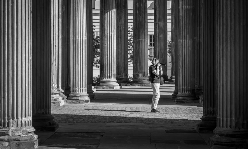 Woman Photographing While Standing By Architectural Columns