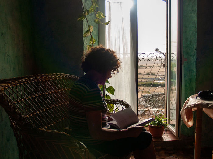 Woman Reading Book White Sitting On Seat At Home