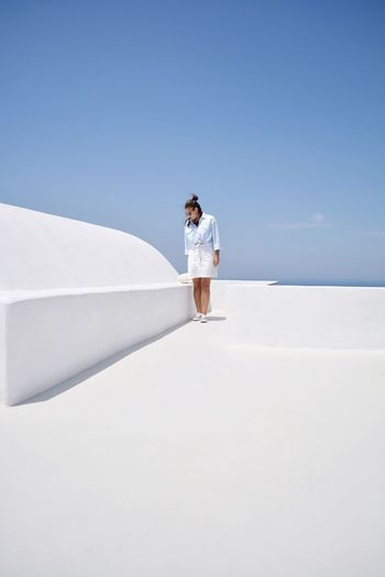 Man standing on white wall against clear sky