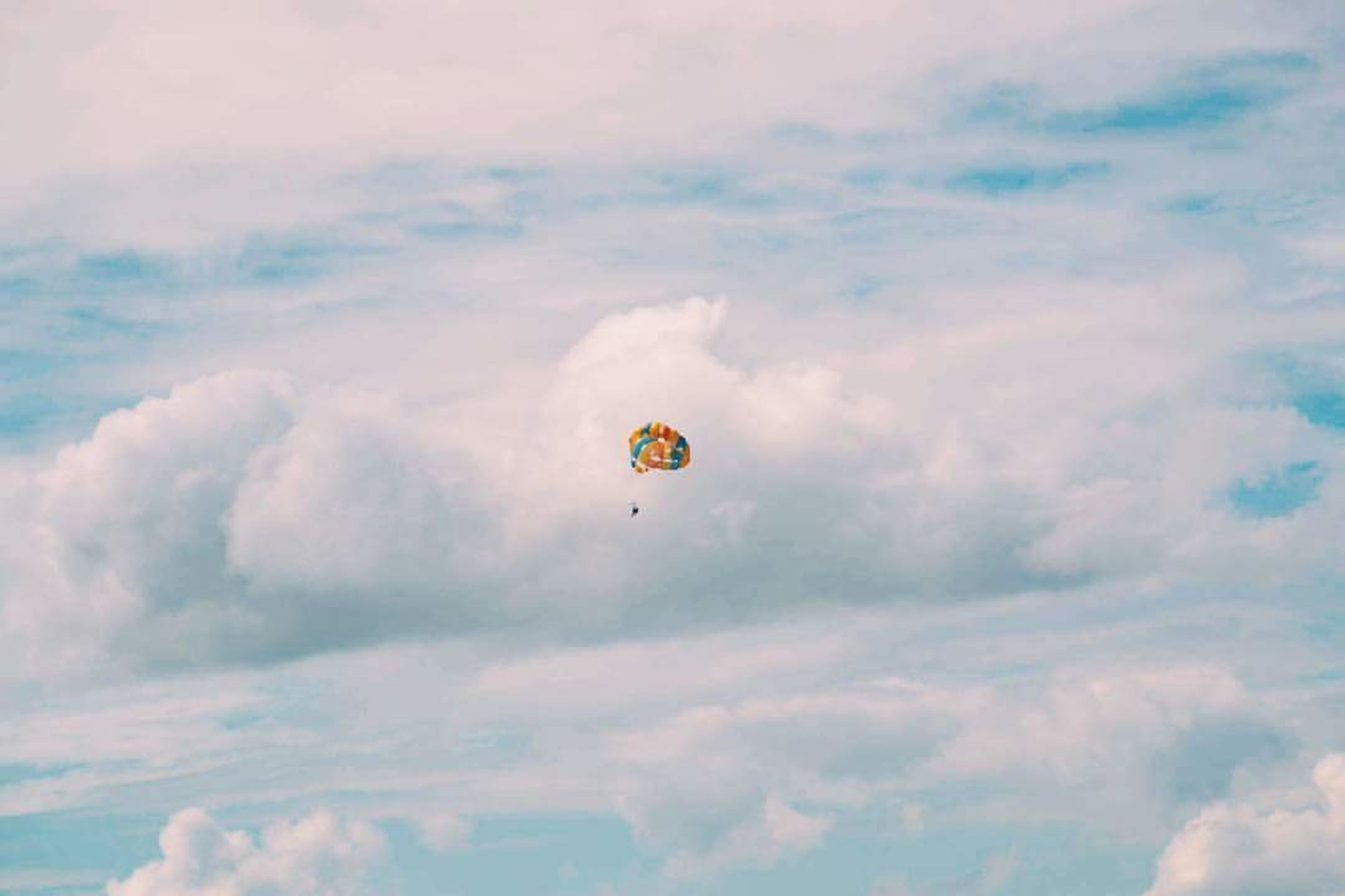 cloud - sky, sky, flying, mid-air, adventure, parachute, paragliding, transportation, extreme sports, low angle view, unrecognizable person, sport, real people, leisure activity, nature, freedom, day, one person, beauty in nature, joy, outdoors, parasailing