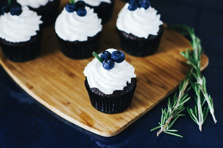 High angle view of blueberry cupcakes on cutting board