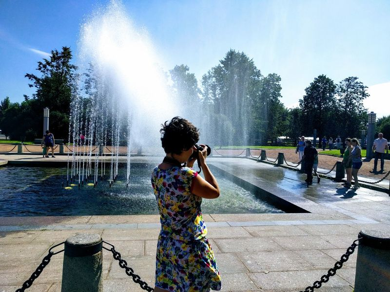 Water Spraying Splashing Fountain Motion Real People Wet Leisure Activity Outdoors Standing Drinking Fountain Girls Sky Lifestyles Day One Person Tree Women Childhood People