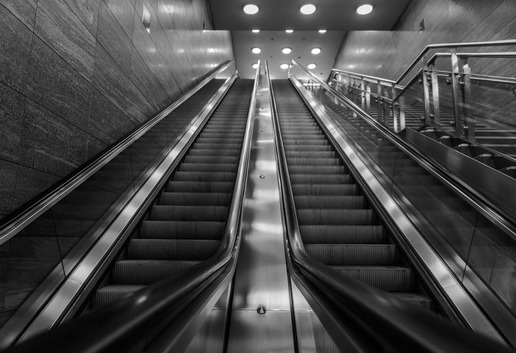 Low angle view of empty steps and escalators at subway station