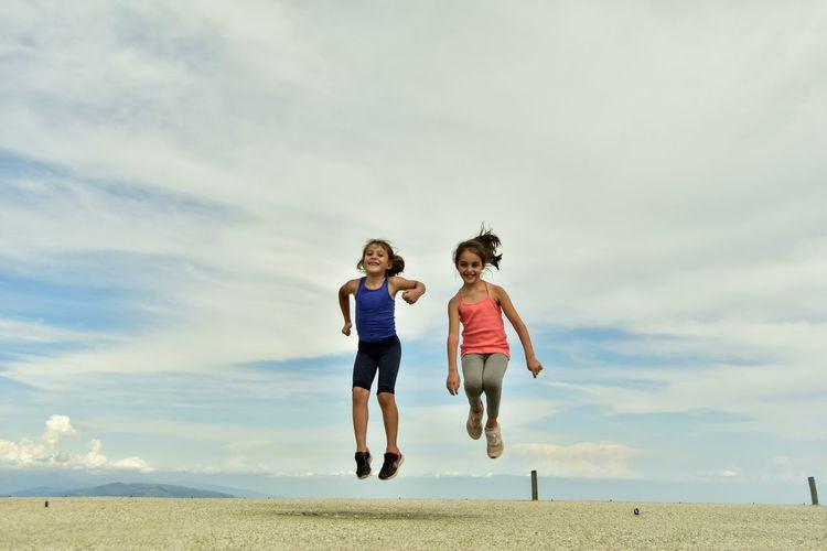 Full length of two girls jumping against the sky