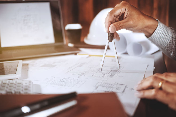 Cropped hand of engineer drawing blueprint in office