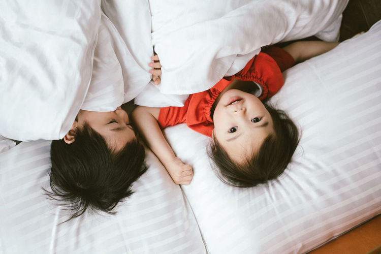 Bed Bedroom Boys Childhood Girls High Angle View Lifestyles Pillow Portrait Real People Relaxation Sleeping Toddler  Togetherness Two People