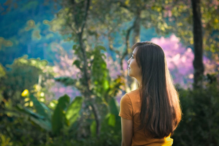 Beautiful woman standing by plants against trees