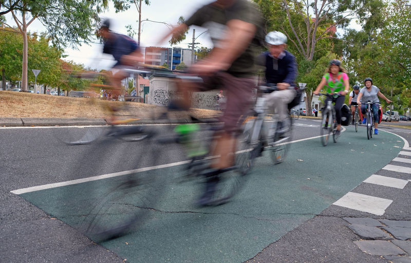 Transportation Blurred Motion Group Of People Motion Real People City Street Road Mode Of Transportation Day Lifestyles People Leisure Activity Speed Bicycle Women Outdoors Riding Commute