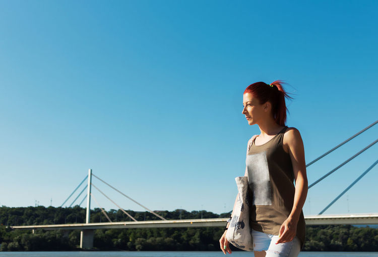 Beautiful woman enjoying in summer day by the river against the sky. copy space.