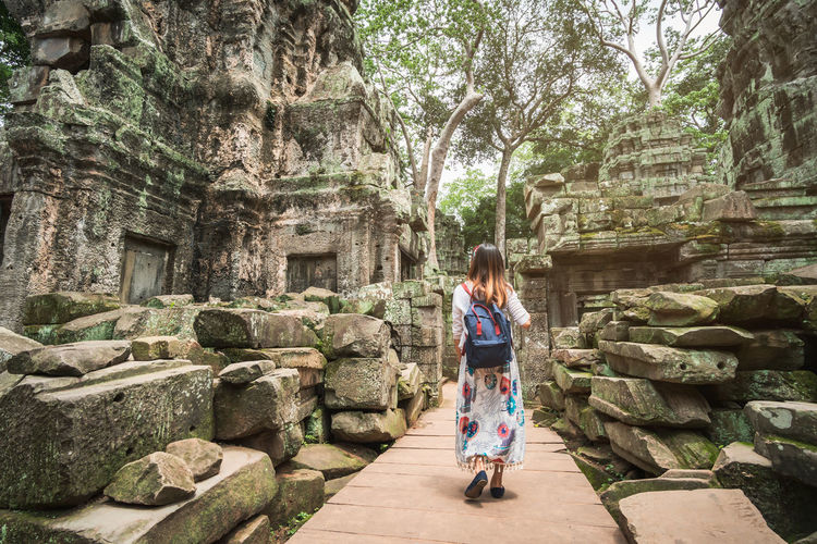 Rear view of woman with backpack walking outside temple