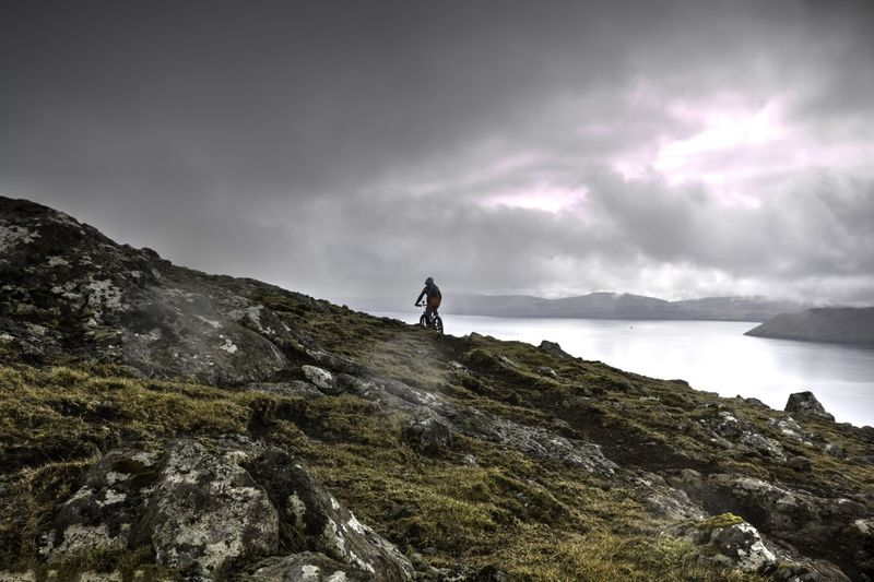 Person Mountain Biking On Rocky Cliff By Lake Against Cloudy Sky