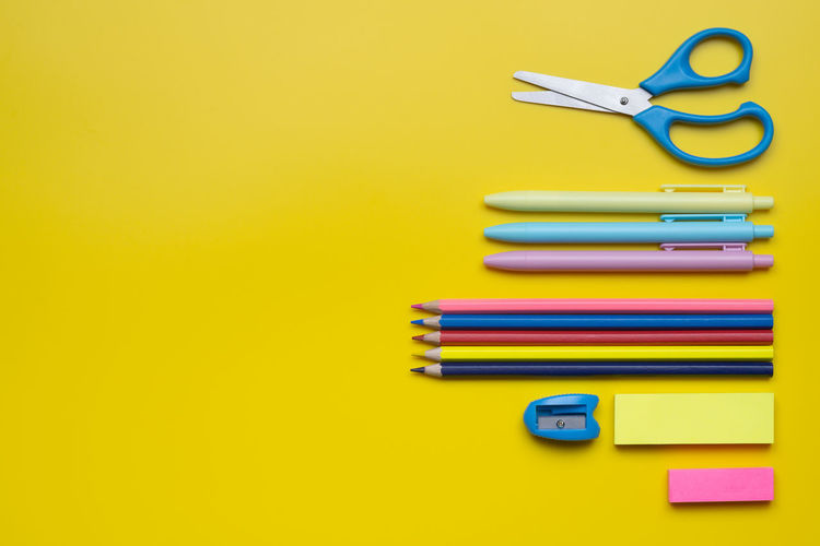 Directly above shot of school supplies on yellow background