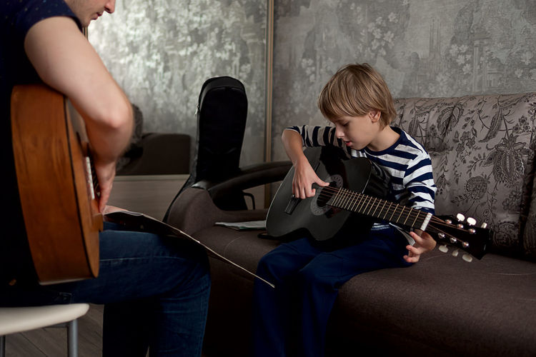 Young male musician teaches little boy student how to play the acoustic guitar and play by notes.