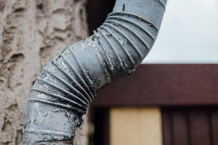 Close-up of old pipe against building