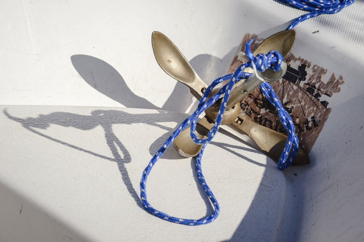 Anchor with blue rope in boat